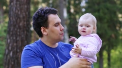 Young handsome man kisses his little cute daughter in summer park - stock footage
