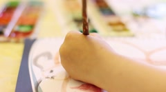 Hand of kid painting in notebook at table Stock Footage
