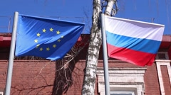 Stock Video Footage of Flags of Russia and European Union waving in wind on street