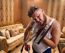 Stock Photo of Bizarre man sings to the vacuum cleaner