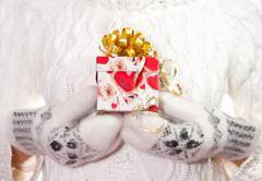 Christmas gift with bow in palms of hands - stock photo