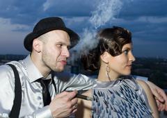Smoking impudent gangster with retro girl Kuvituskuvat