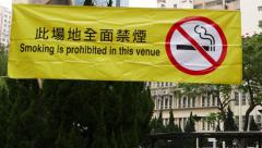 No smoking area sign on the yellow poster in public park, slide shot - stock footage
