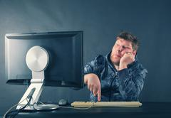 Man sitting at desk looking on computer screen - stock photo