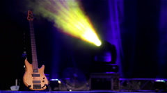 A bass guitar on a stage with blue woven at background Stock Footage