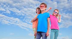 Group of happy friends wearing eyeglasses against blue sky - stock photo