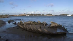 Barges sailing on the river Rhine, ancient ship wreck in foreground Stock Footage