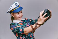 Girl in captain cap makes self camera Stock Photos