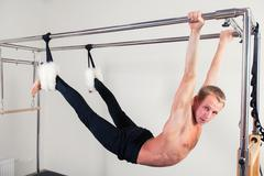 Pilates aerobic instructor man in cadillac fitness exercise - stock photo