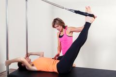 Pilates aerobic instructor woman with in cadillac fitness exercise Stock Photos