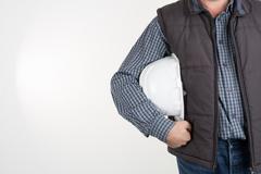 Construction worker hands holding white plastic helmet isolated on white back - stock photo