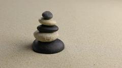 Stones pyramid on sand symbolizing zen - stock footage
