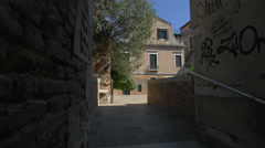 Tourists walking near a small garden surrounded by the Venetian apartments - stock footage