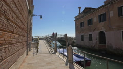 Two people standing on a bridge over Rio de la Fornace in Venice Stock Footage