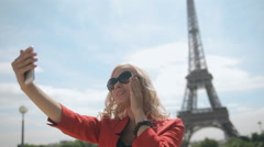 Attractive blonde in sunglasses doing selfie against the backdrop of the Eiffel Stock Footage