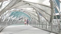 Helix Bridge. Marina Bay, Singapore. A couple of tourists walking on bridge Stock Footage