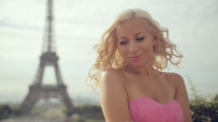 Beautiful girl in a pink festive dress sitting on a background of the Eiffel Stock Footage