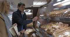 Man and woman buying delicious bun in the shop Stock Footage