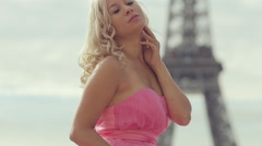 Gorgeous young woman in a magnificent pink dress posing near the Eiffel Tower Stock Footage