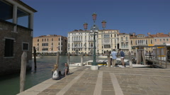 Four tourists relaxing while boats are sailing near Fondamenta Salute, Venice Stock Footage