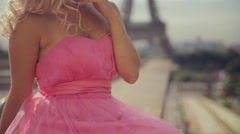 Stock Video Footage of Thoughtful woman dressed in festive pink strapless dress near the Eiffel Tower