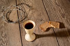 Chalice and bread on the wooden table - stock photo