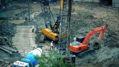 Workers With Cement Mixer And Excavators On Construction Site Stock Footage