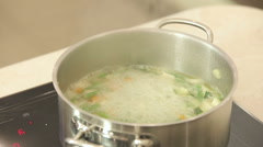 Chef is putting pasta into a boiling pot of vegetable soup - stock footage