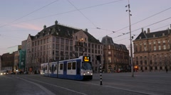 Royal Palace on Dam Square in Amsterdam as a local tram passes Stock Footage