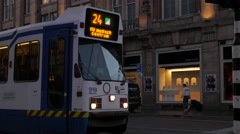 Tram pulls away from stop on Damrak, Amsterdam Stock Footage