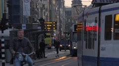 Trams cross paths on Damrak in Central Amsterdam Stock Footage
