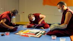 three Tibetan monks creating sand Mandala - stock footage
