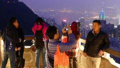 Asian tourists take pictures of amazing night panoramic city view Stock Footage