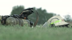 Fire Fighters helmet and air pack on the eground Stock Footage