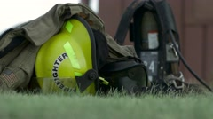Several Fire Fighters helmet and air pack on the ground Stock Footage