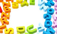 A border of rainbow colored wooden alphabet blocks - stock photo