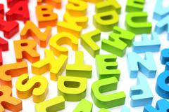Rainbow Alphabet scattered on a white background - stock photo