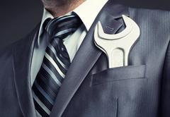 Businessman with spanner Stock Photos