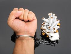Hand locked to cigarettes Stock Photos