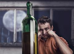 Drunk man looks at the bottle - stock photo