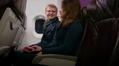 Happy young man and woman flying on plane with comfort, holding hands, talking Stock Footage