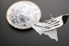 Piece of torn agreement on the fork - stock photo