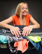 Woman struggles to shut a full suitcase Stock Photos