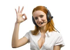 Beautiful smiling business woman with headset shows OK sign Stock Photos