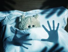 Adorable teddy bear laying in bed, scared Stock Photos