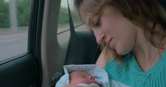 Woman with baby in arms riding a car Stock Footage