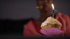 Focus pull from cupcake to sad female on her 30th birthday, in slow motion Stock Footage