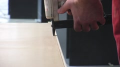 Worker using staple gun to fix back side of the closet in furniture factory. - stock footage