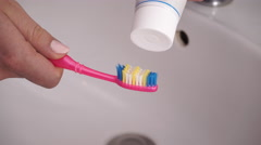 Woman hands holding toothbrush and placing toothpaste on it 4K Stock Footage