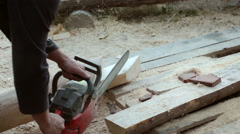 Carpenter carving timber with chain saw - stock footage